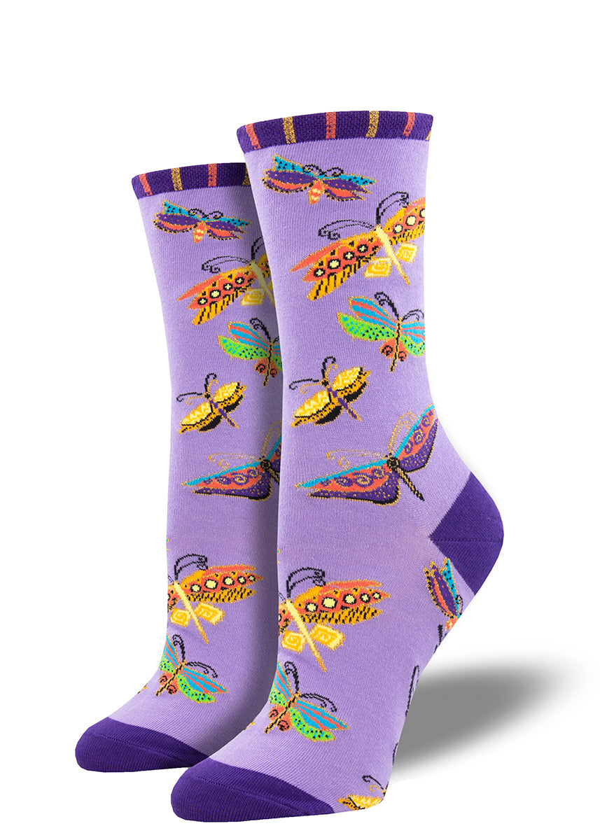 Laurel Burch socks for women are covered in colorful butterflies and dragonflies on a light purple background.