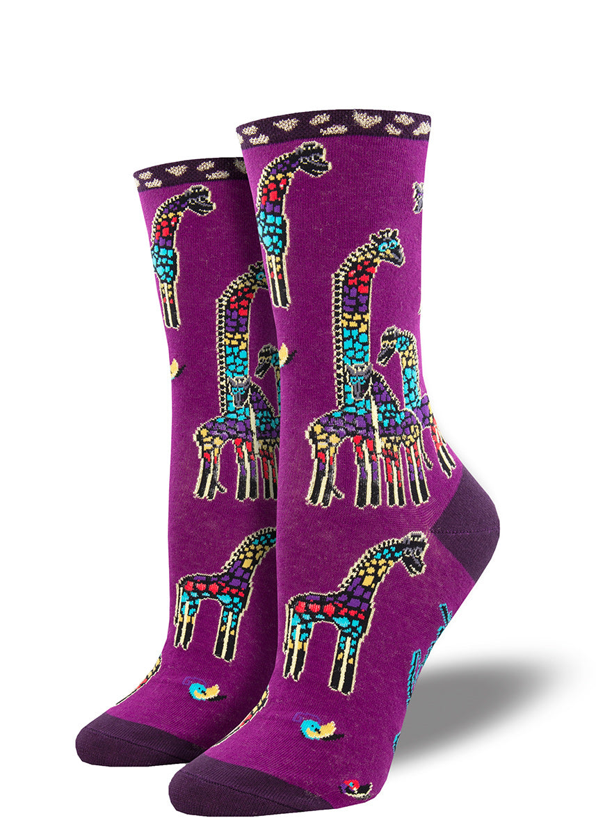 Laurel Burch socks for women feature funky multicolored giraffes on a grape-colored background.