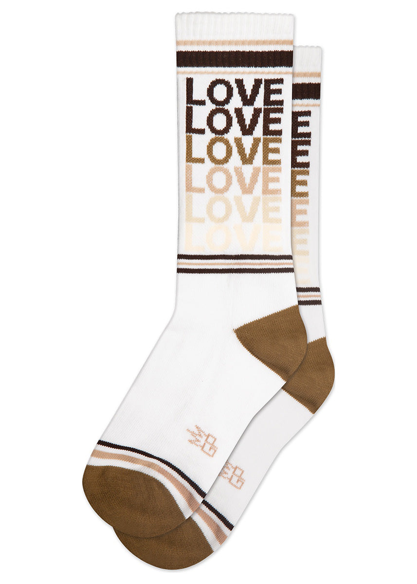 "Athletic-style unisex socks show the word ""LOVE"" repeated in an array of different skin tone colors."