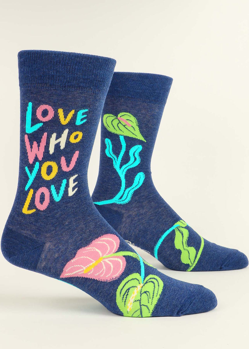 "Crew socks for men say ""Love Who You Love"" in colorful letters with an abstract leaf design."