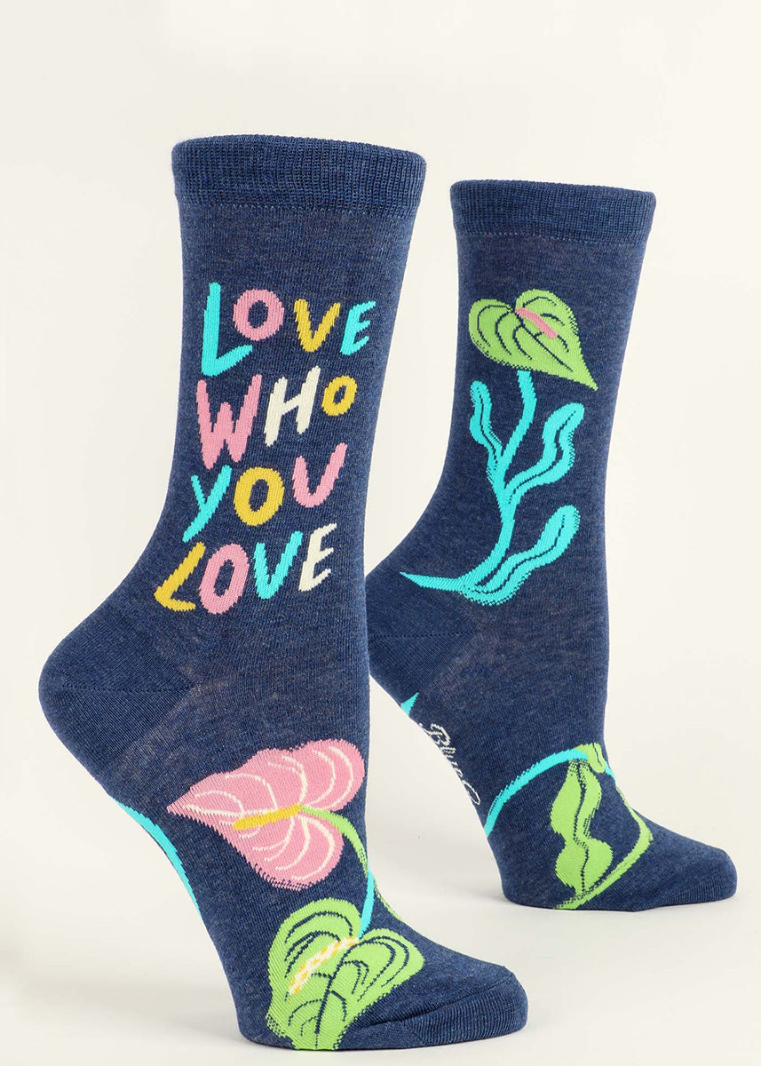 "Crew socks for women say ""Love who you love"" in colorful pastel letters with an abstract floral design."