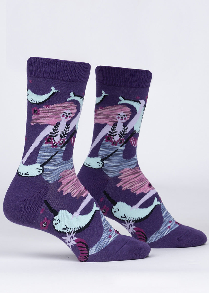 Crew socks for women feature magical mermaids underwater with their narwhal friends on a dark purple background.