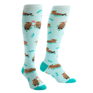 Smiling otters float about this knee high sock, holding hands and cuddling their young.