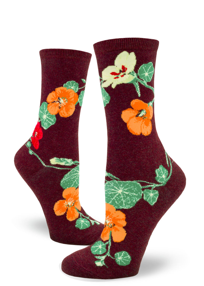 Crew socks for women with yellow, orange, and red nasturtium flowers on a dark red background.