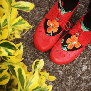 Orange nasturtium flowers on the feet of ModSocks' beautiful floral knee socks.