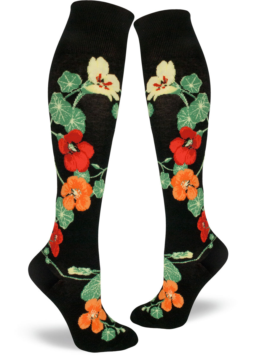 Knee-high socks with nasturtiums in bright orange, red and yellow on a black background