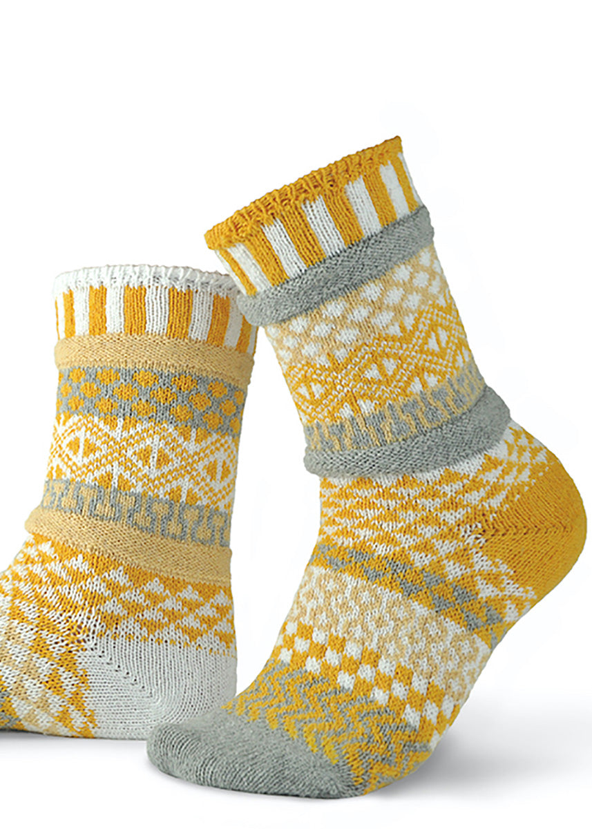 Mismatched pattern socks in shades of yellow, white and gray.