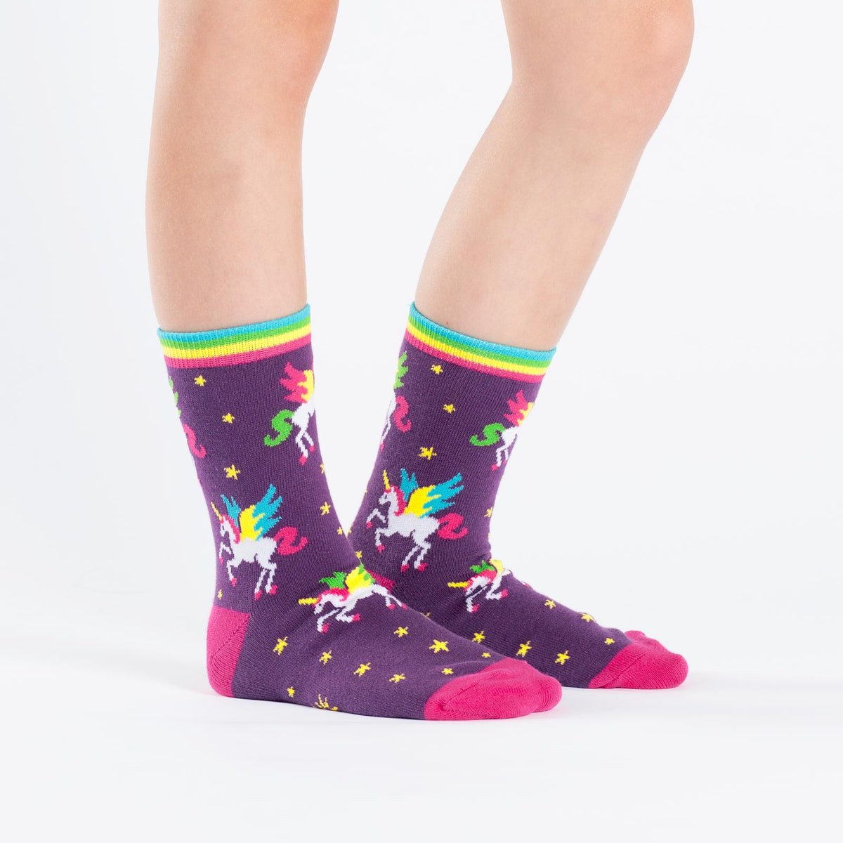 Winged rainbow unicorn socks for kids with mythical creatures flying through a purple sky.