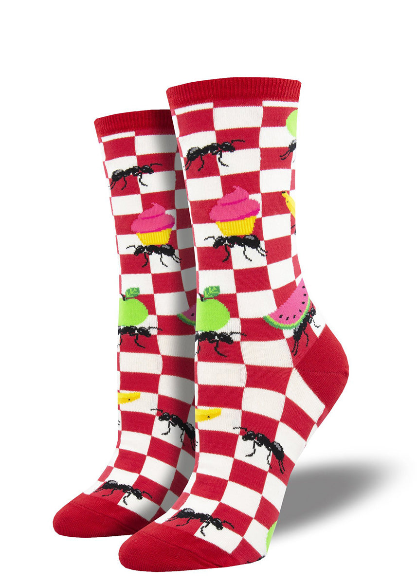 Funny summer socks for women show ants carrying away cupcakes, apples, watermelons, and more from a checkered picnic blanket.