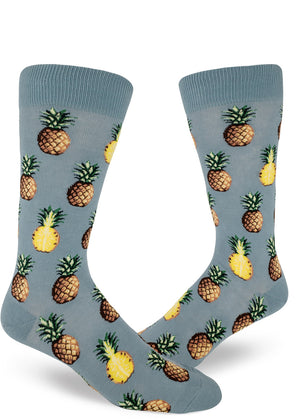 Tropical pineapple socks for men with pineapples sliced in half or whole on a slate blue background