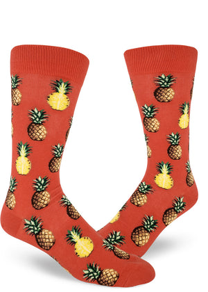 Tropical pineapple socks for men with pineapples sliced in half or whole on a coral red background