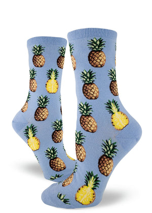 Tropical pineapple socks for women with pineapples sliced in half and whole pineapples on a light blue background