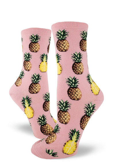 Tropical pineapple socks for women with pineapples sliced in half and whole pineapples on a light pink background