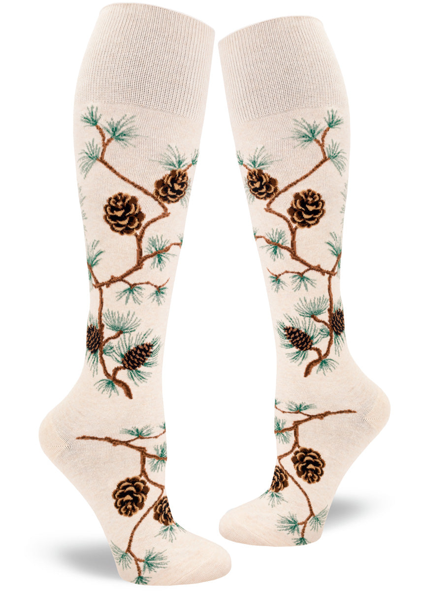 Knee high socks for women feature bending pine branches covered in pinecones and pine needles.