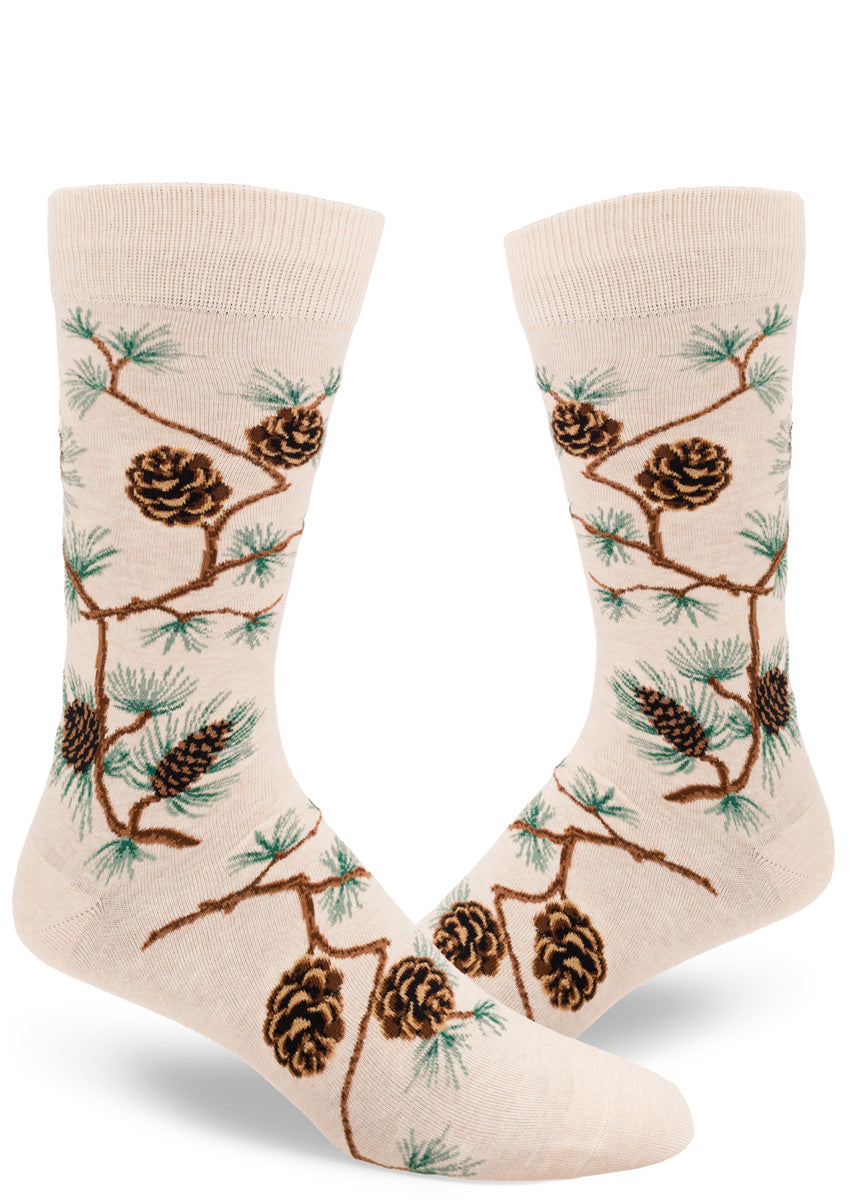Nature socks for men feature pinecones on their branches on a cream background.