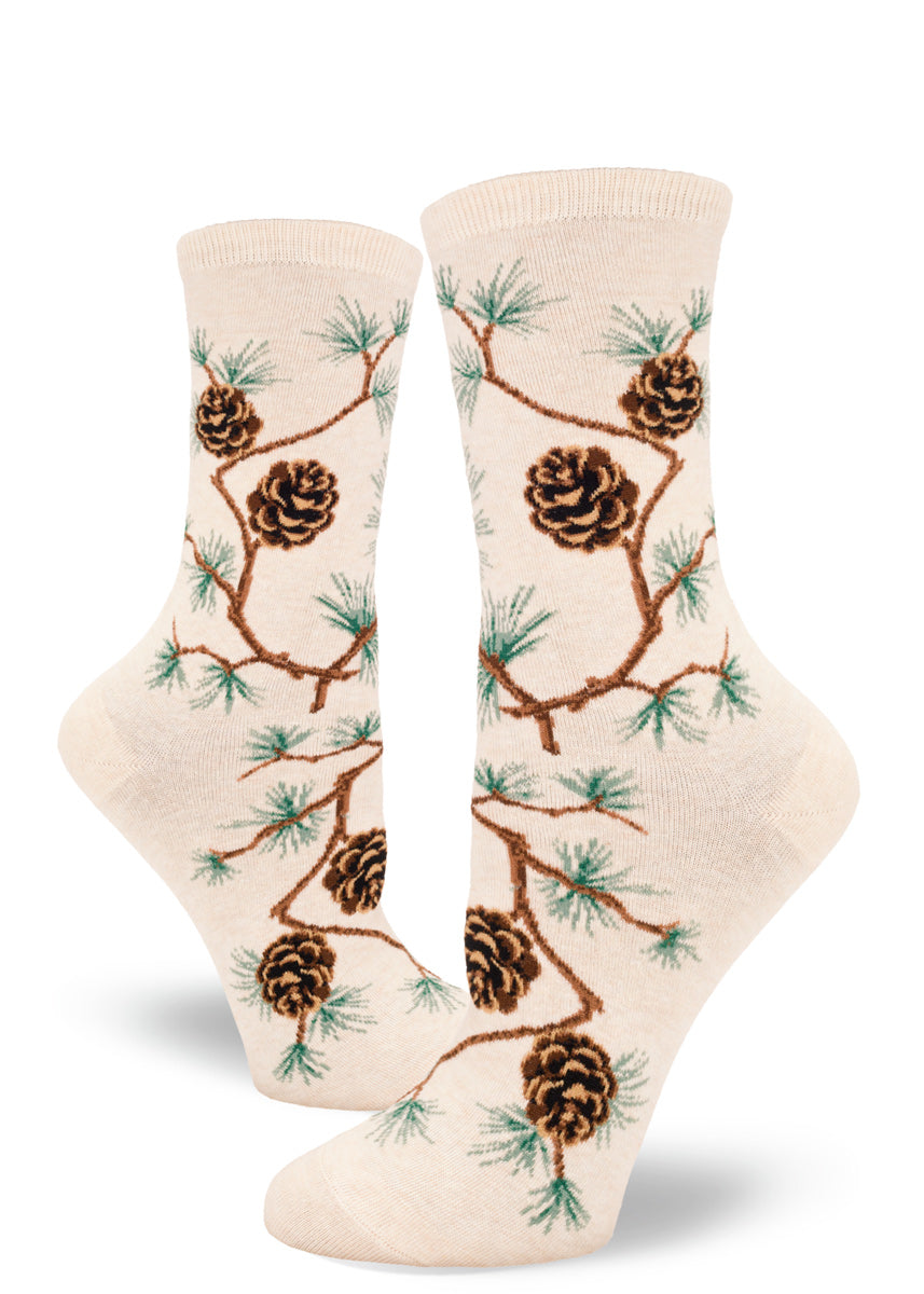 Crew socks for women feature pine branches with green needles and brown pinecones on a cream background.