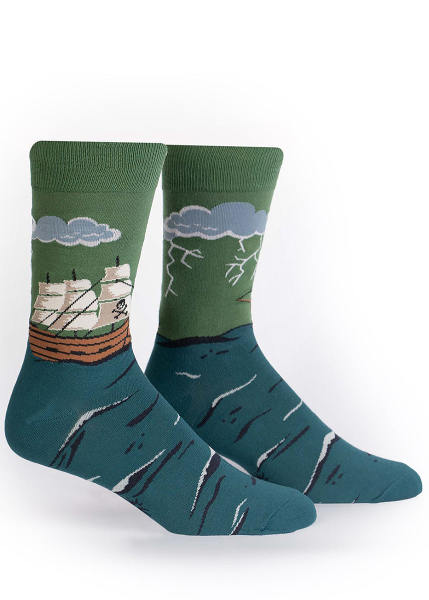 Socks for men show a pirate ship sailing on a dark teal sea with a stormy green sky overhead.
