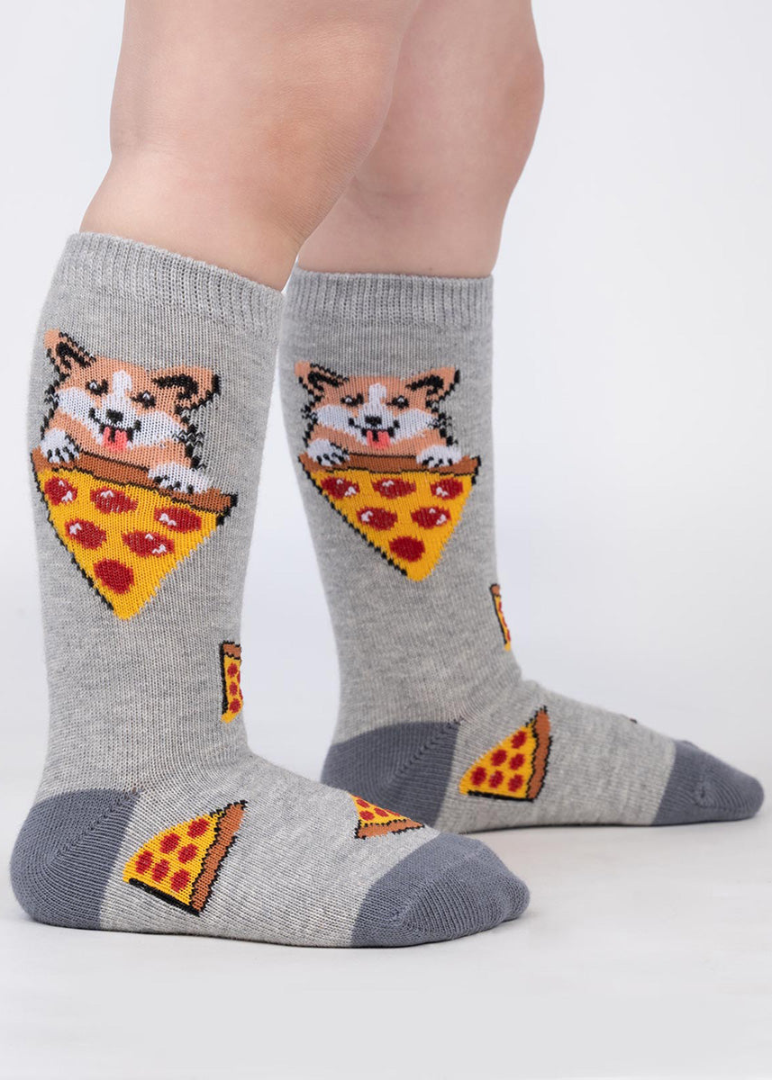 Knee-high socks for toddlers feature adorable corgis holding slices of pizza.