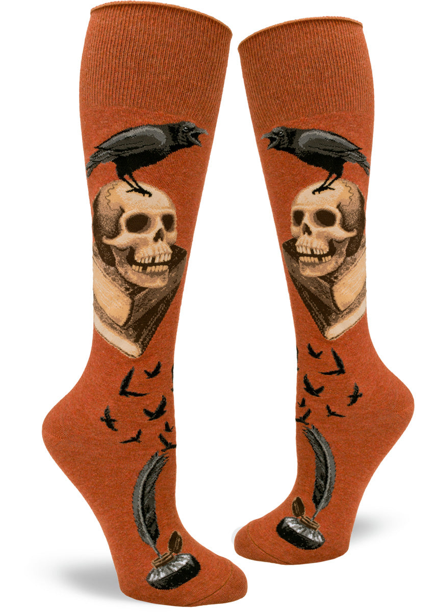 A raven caws from atop a human skull and a pile of books on these spooky knee-highs for women.