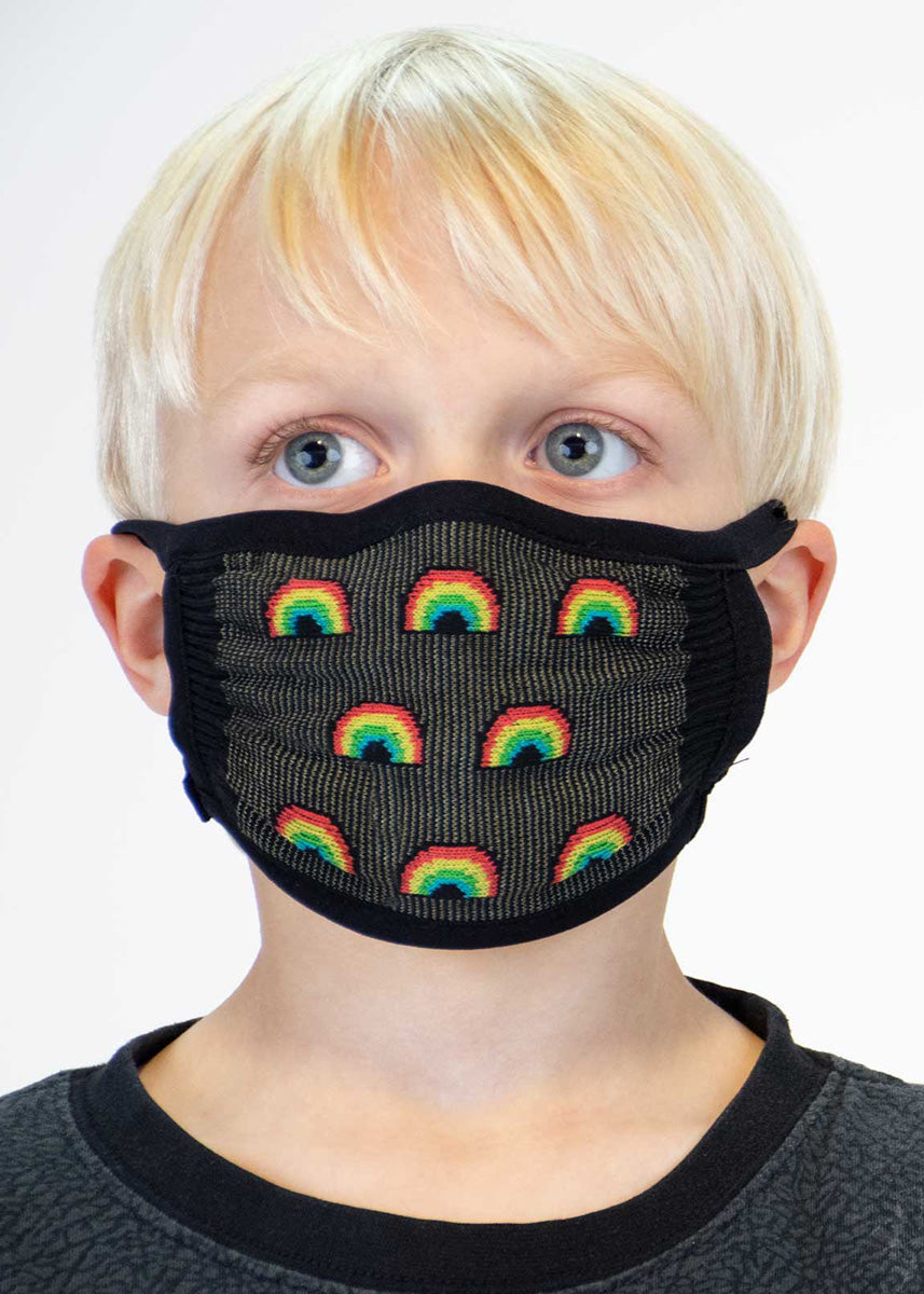 A black face mask with a pattern of rainbows on a little blonde boy.