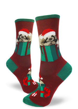 Cute Christmas sloth socks for women with sloths in Santa hats laying on Christmas presents with a dark red background