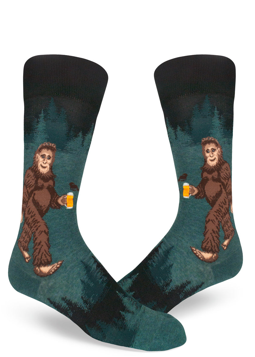 Sasquatch beer socks for men with a bigfoot drinking beer in the woods with trees behind him