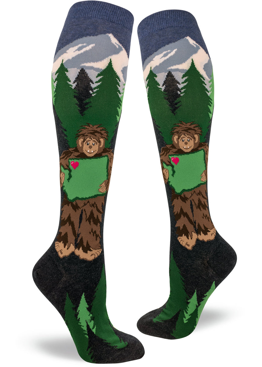 On Sasquatch Loves Washington knee-high socks, Bigfoot holds Washington state with trees and mountains