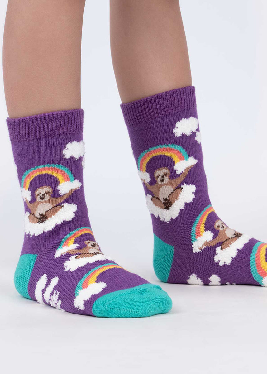 Cute animal socks for kids show sloths sitting on clouds and holding a rainbow between their paws.