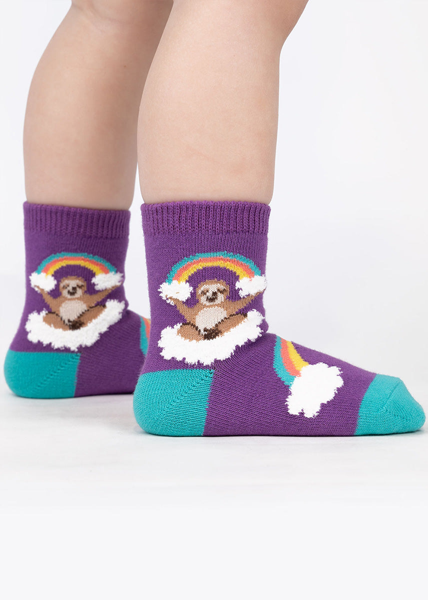 Socks for toddlers show adorable sloths holding rainbows and resting on clouds.