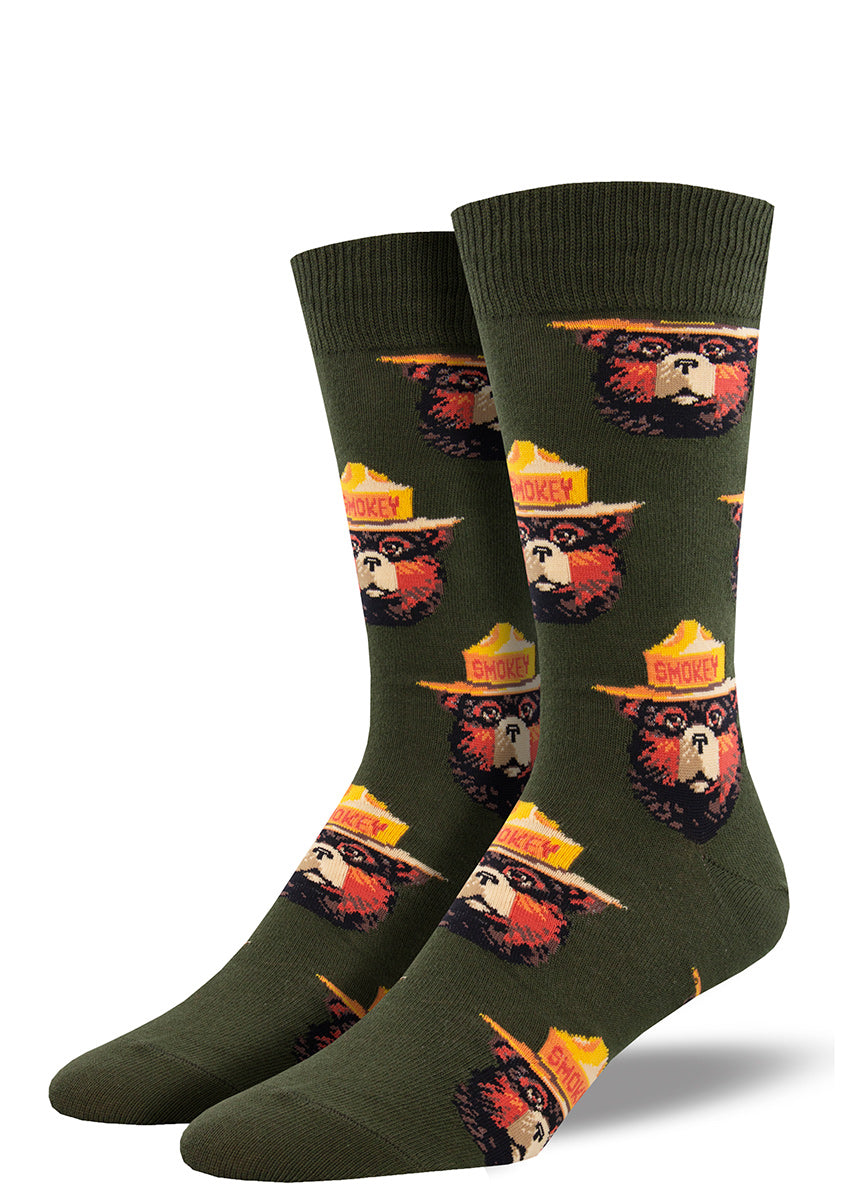 Crew socks for men feature an all-over design of Smokey Bear in his signature hat on a olive green background.