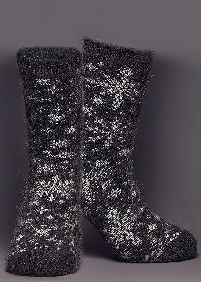 Winter socks for women are made of 80% goat wool and feature a design of white snowflakes on a dark gray background.