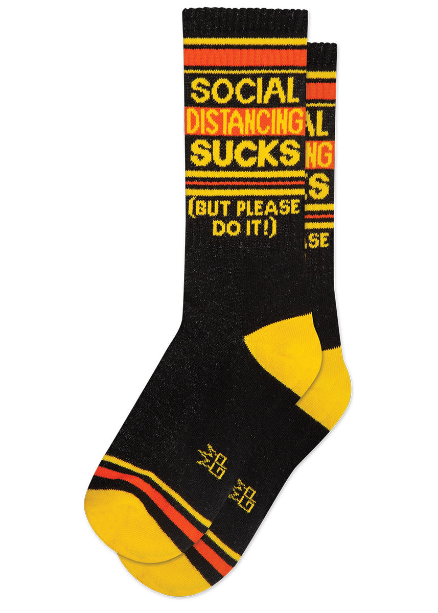 "Funny gym socks say ""Social Distancing Sucks (But Please Do It!)"" with bright yellow and orange stripes on a black background."