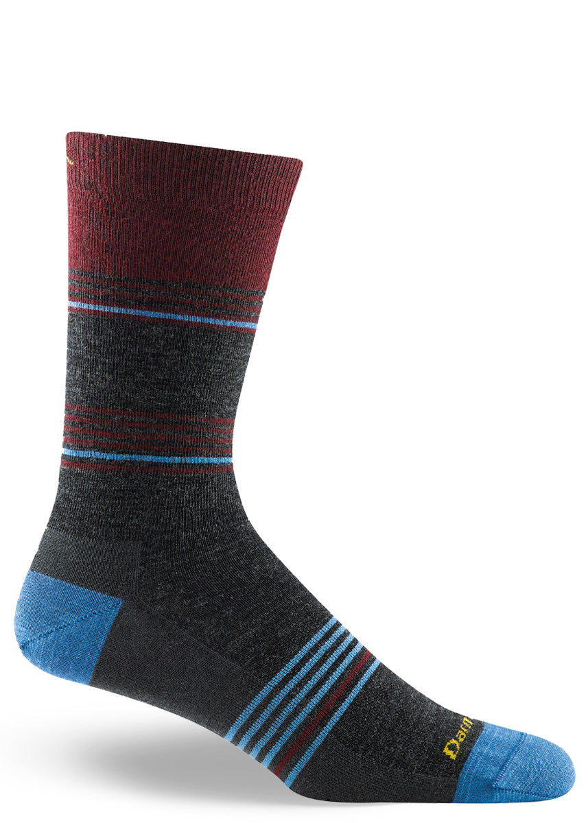 Wool socks for men come in a crew length with a burgundy and light blue stripe design on a charcoal background.