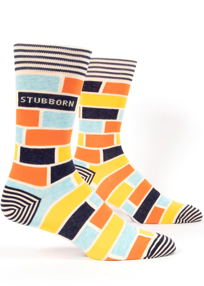 "Funny socks for men feature an orange and blue brick design with the word, ""Stubborn."""