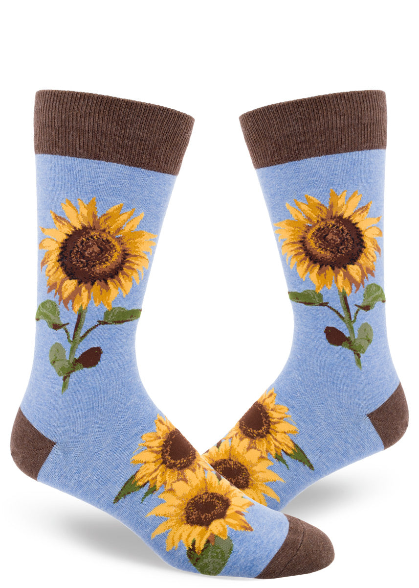 Sunflower socks for men feature realistic golden sunflowers on a light blue background with brown cuffs, toes, and heels.