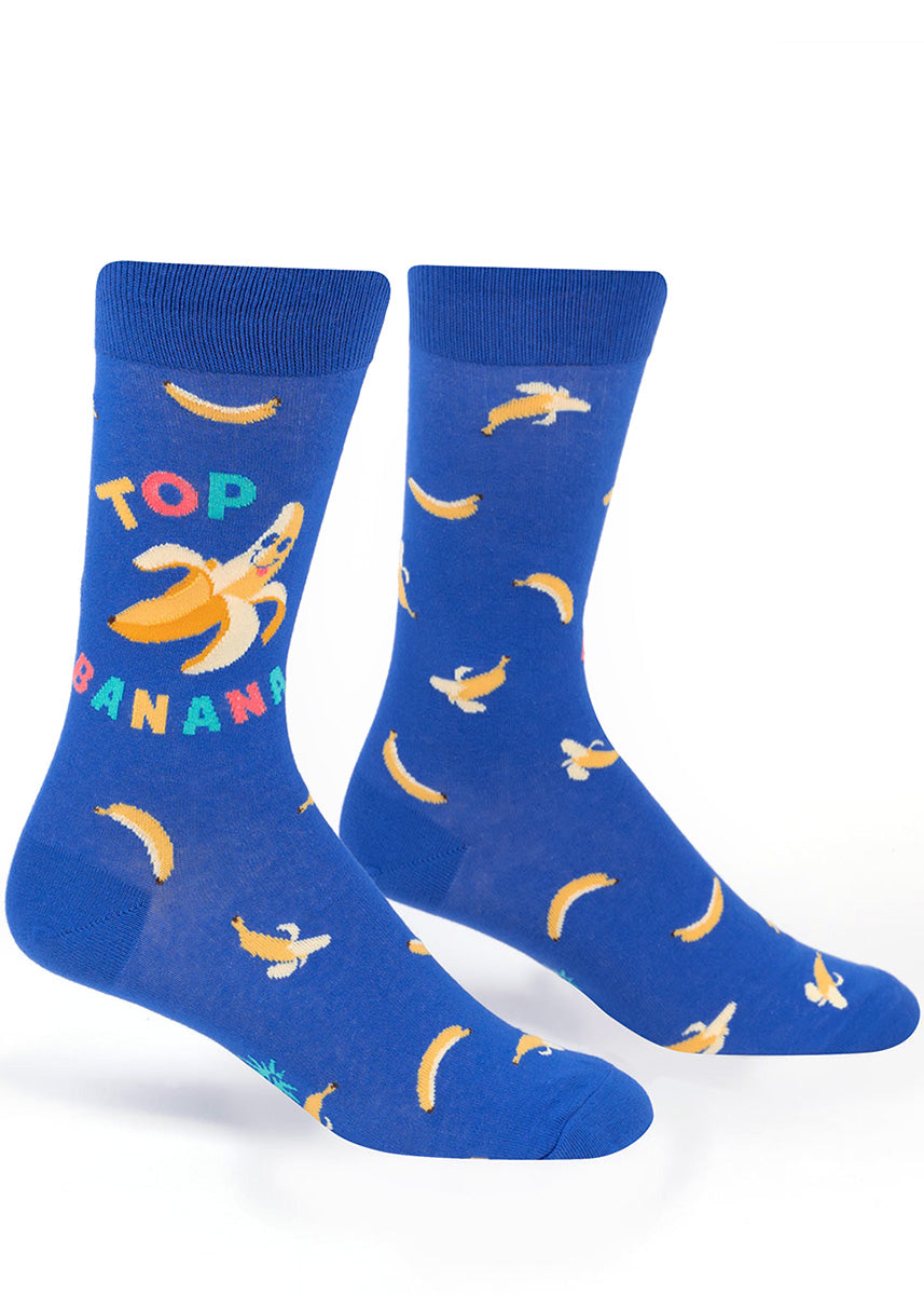 "Funny food socks for men show a smiling banana with the words ""Top Banana"" on a bright blue background."