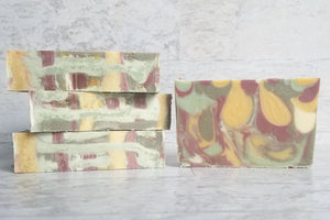 Multi colored artisan cold process soap with red, yellow, white, and green drop swirls and the top looks like woven tweed.