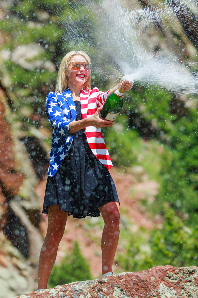 Woman Popping Champagne In American Flag Suit Jacket
