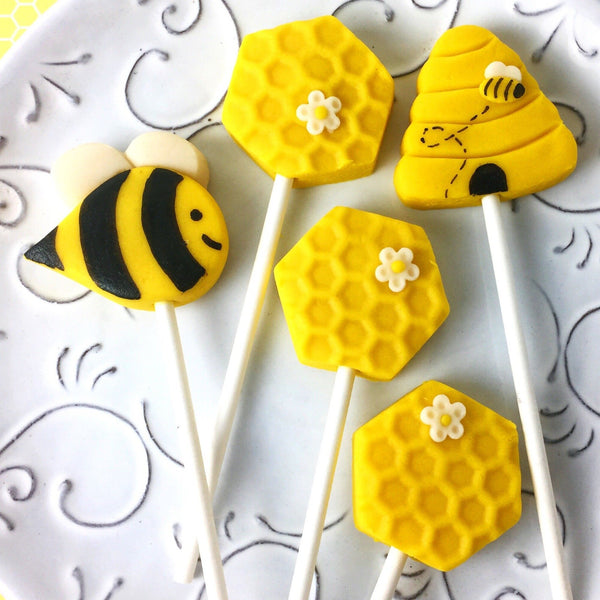 Rosh Hashanah honeybee collection with bees, beehives and honeycomb marzipan candy lollipops on a plate