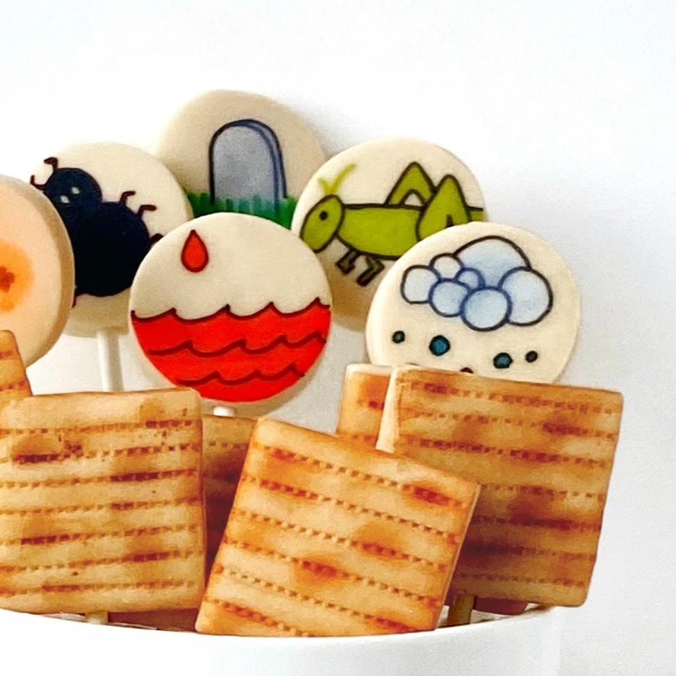 Passover Seder super set with many apples and ten plagues with frogs marzipan candy lollipops close up