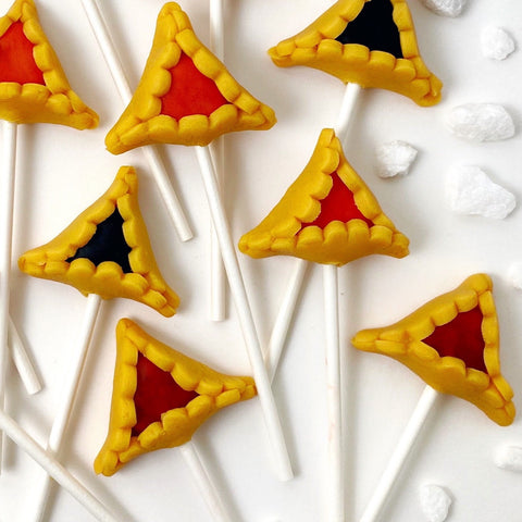 Purim vegan gluten-free assorted hamantaschen marzipan candy lollipops closeup