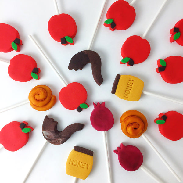 Rosh Hashanah collection candid shot with apples, honey, shofar, challah and pomegranate marzipan candy lollipops