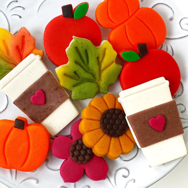 Autumn collection with pumpkins, coffee cups, flowers, maple leaves and apples marzipan candy tiles close up