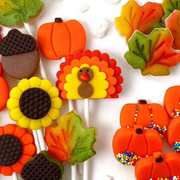 Thanksgiving ultimate collection with pumpkins, turkeys, sunflowers, maple leaves and acorns marzipan candy lollipops sprinkles closeup