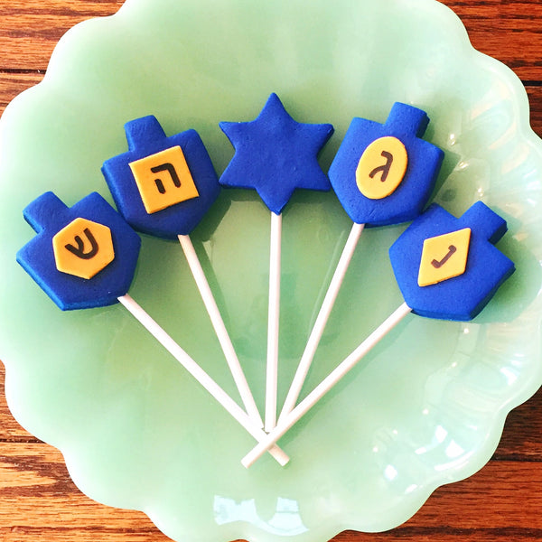 Hanukkah blue dreidels with gold letters in menorah shape marzipan candy lollipops in a candid shop