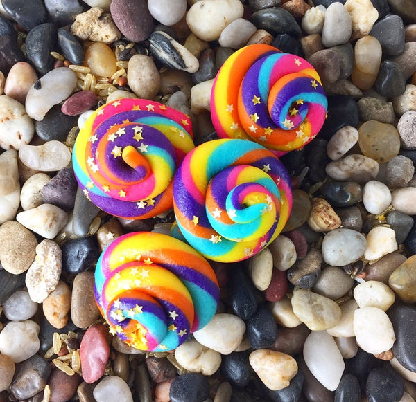 rainbow unicorn poop marzipan candy sculpture treats on a bed of rocks