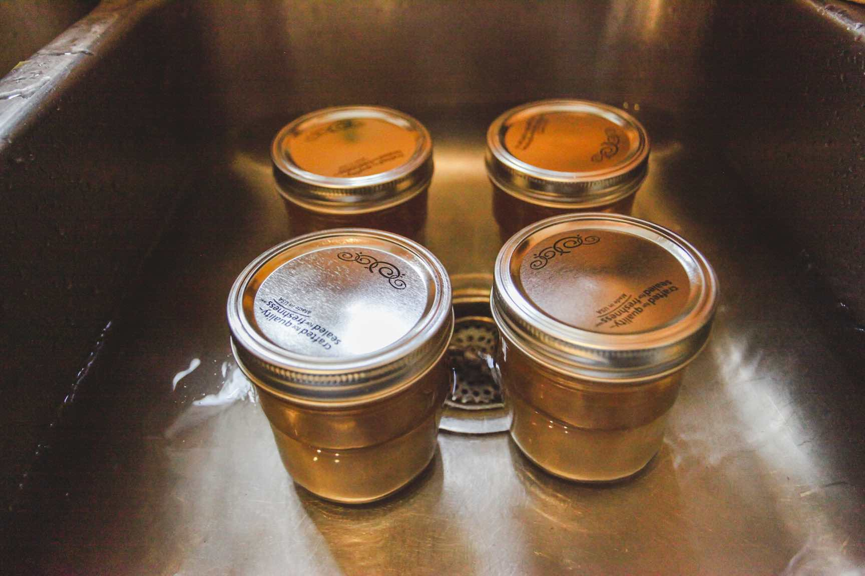 cooling homemade bone broth in a water bath in canning jars