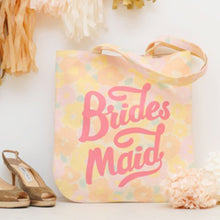 A floral tote bag with the word Bridesmaid printed in pink on the front surrounded by wedding decorations