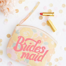 Floral pouch with the word Bridesmaid printed in a hand lettering style in pink on the front on a wedding table