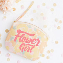 A pastel floral canvas pouch with the words flower girl printed in pink on the front in a hand drawn lettering style placed on a table surrounded by confetti at a wedding